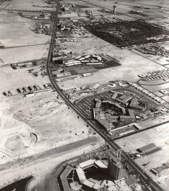 Sands hotel tower can be seen under construction in the upper middle part of the photo. Lower left, the beginnings of Caesars Palace. On the far lower right, Three Coin Motel and Galaxy Motel._1965